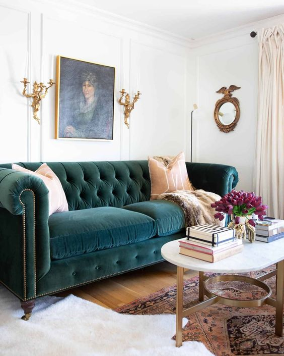 a sophisticated living room with a teal velvet Chesterfield sofa, gold candelabras and a table plus a bold artwork
