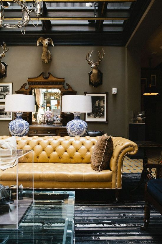 a sophisticated living room with a yellow leather Chesterfield sofa, taxidermy, plexiglass items and refined lamps