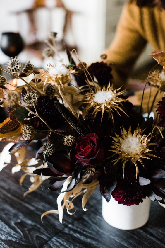 a statement Halloween floral arrangement with deep burgundy roses, dried blooms and leaves looks wow