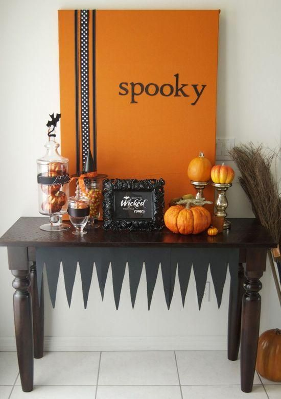 a stylish black and orange Halloween console with an artwork, faux pumpkins and glass jars with candies