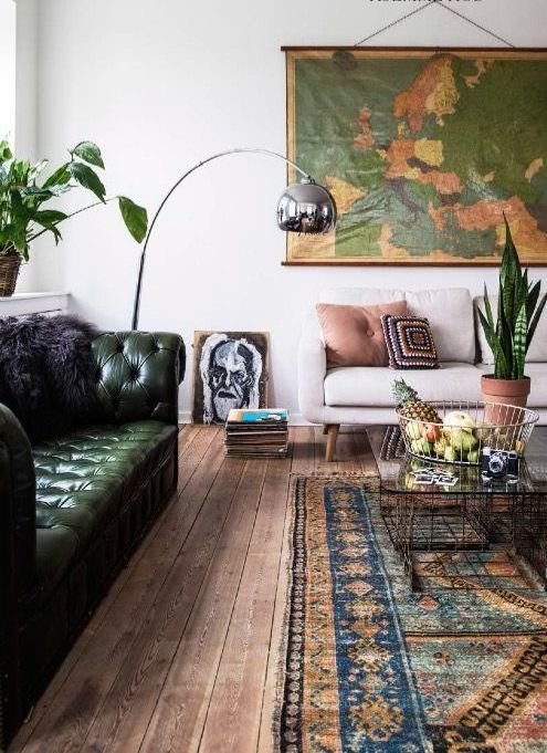 a stylish living room done with a green leather Chesterfield sofa, a vintage map, a bold boho rug, some plants and a floor lamp