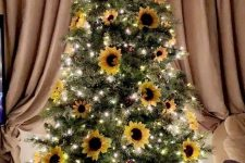 a sunflower Thanksgiving tree with lights, pinecones, blooms and a large taupe bow on top