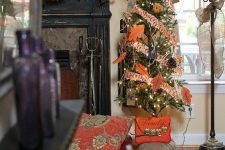 a thankful tree with bright printed ribbons, faux leaves, pinecones, twine, lights and a large plaid bow on top
