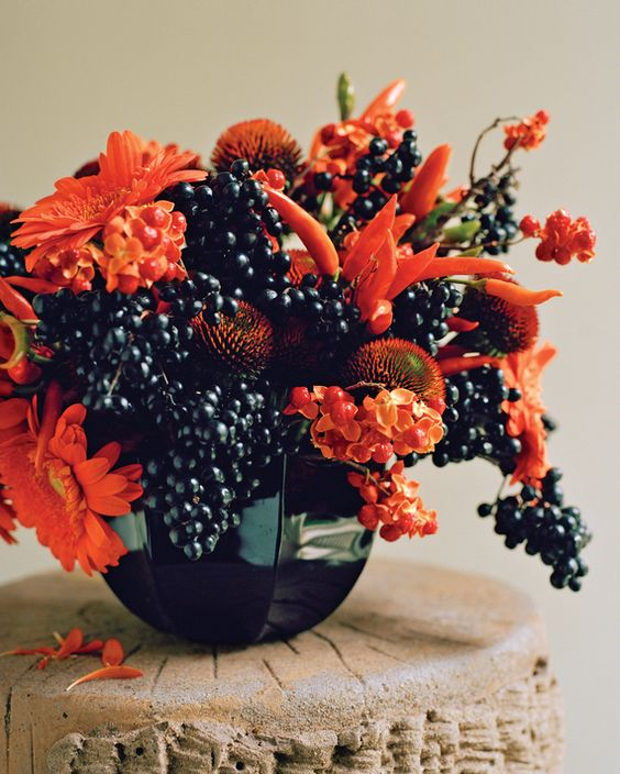 a very sumptuous floral arrangement for Halloween of orange blooms, berries and peppers looks fantastic
