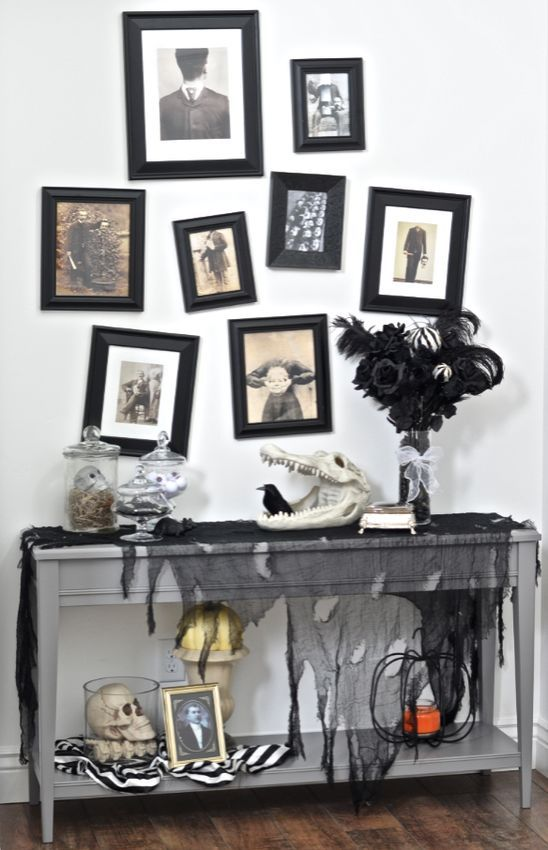 a vintage Halloween console table with black tulle, skulls and black roses plus a gallery wall with scary pics