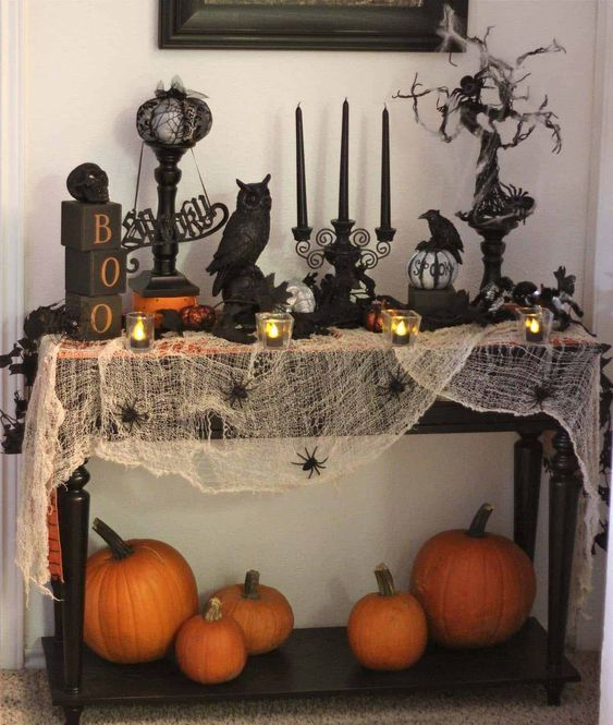 a vintage Halloween console with black candles, black birds, a spooky tree, some letters and spiderweb with spiders