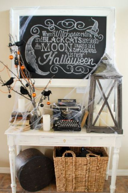 a vintage Halloween console with branches with blackbirds, ornaments, a candle lantern and lots of spiderweb
