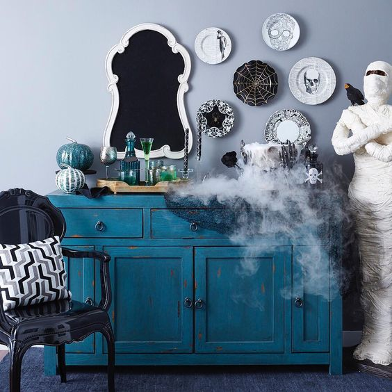a vintage blue console table with a white and turquoise pumpkin, an assortment of black and white decorative plates and smoke coming from the cauldron
