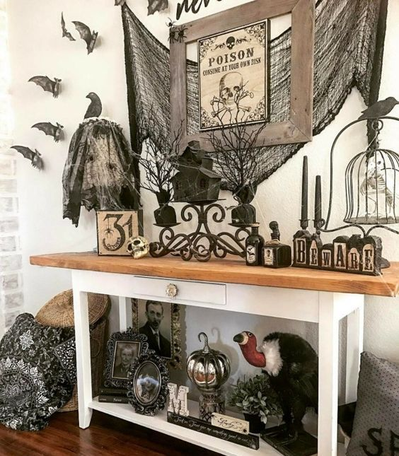 a vintage farmhouse console with lots of bats and birds, spiderweb, vintage artworks and signs and black candles