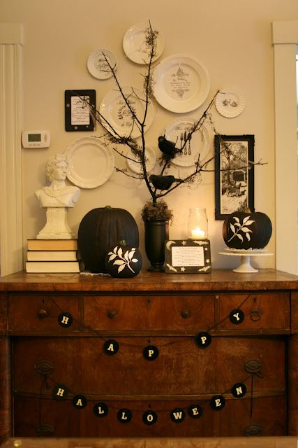 a vintage inspired display with black and white pumpkins, buntings and blackbirds on branches