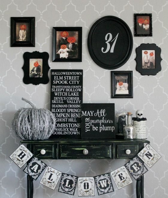 a vintage rustic console table with a bunting, a vine pumpkin, a gallery wall and some skulls is veyr stylish