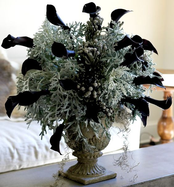 a vintage urn with pale greenery, berries and black calla lilies is a stunning and bold Halloween centerpiece