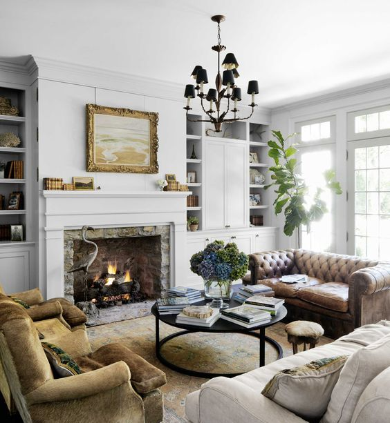 a welcoming and chic living room with a brown leather Chesterfield sofa, a neutral one, tan velvet chairs and a real working fireplace