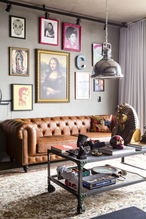 a whimsical industrial living room with a brown leather Chesterfield sofa, a bold and quirky gallery wall and a metal table