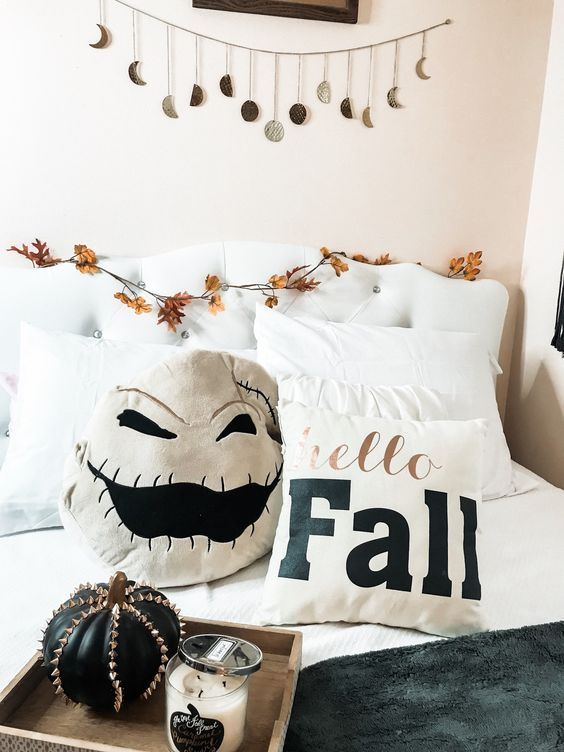 add a scary pillow, a spiked pumpkin and a moon phase garland over the bed to make your bedroom more Halloween-like