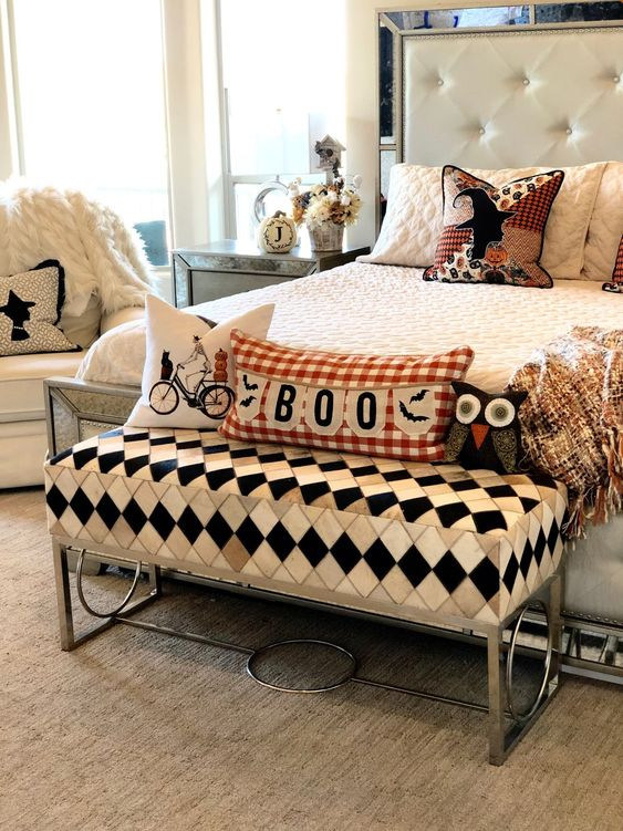 an elegant and refined bedroom in neutrals, with vintage pillows and a cathy ottoman for Halloween