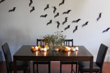 black paper bats on the wall, candles, mini pumpkins and a greenery arrangement for minimal Halloween styling