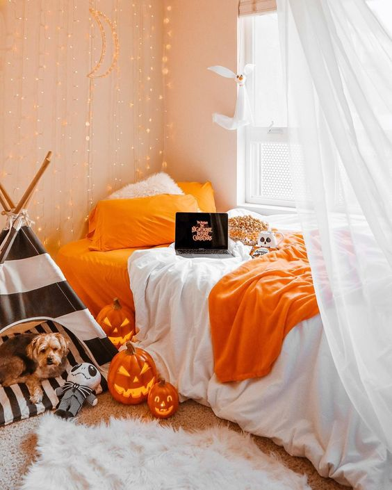 carved pumpkin lanterns, a black and white teepee for the dog, bright orange bedding and lights