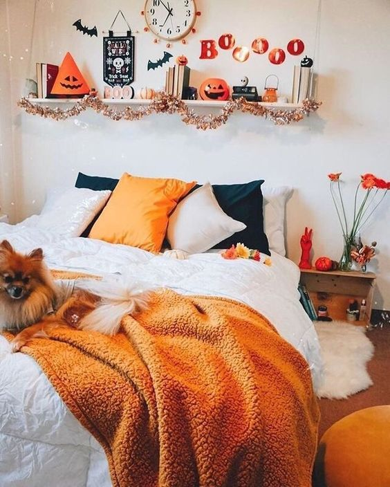 chic and easy Halloween bedroom decor with orange and black pillows, an orange blanket, brigth letters, pumpkins and letters