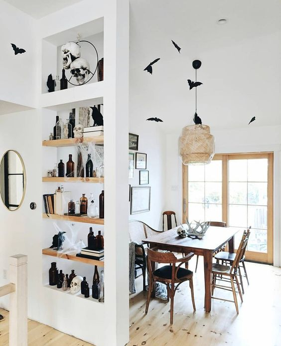minimalist Halloween decor with black bats here and there, skulls, antlers and spiderwebs