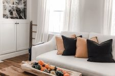 minimalist Halloween decorating with orange and black pillows, faux pumpkins and gourds in a wooden bowl and spiderwebs