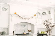 minimalist Halloween kitchen styling with a letter banner, pumpkins – natural and velvet ones, green apples in a cauldron