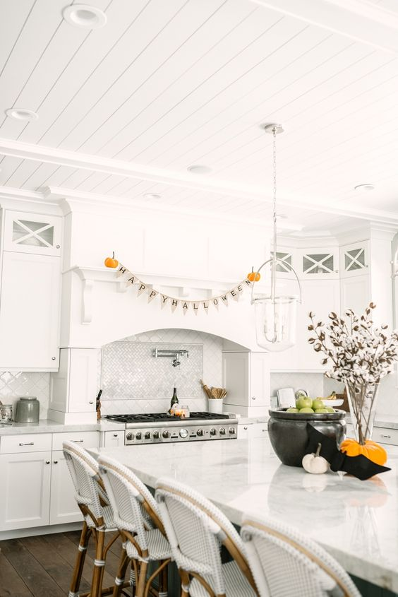 minimalist Halloween kitchen styling with a letter banner, pumpkins - natural and velvet ones, green apples in a cauldron