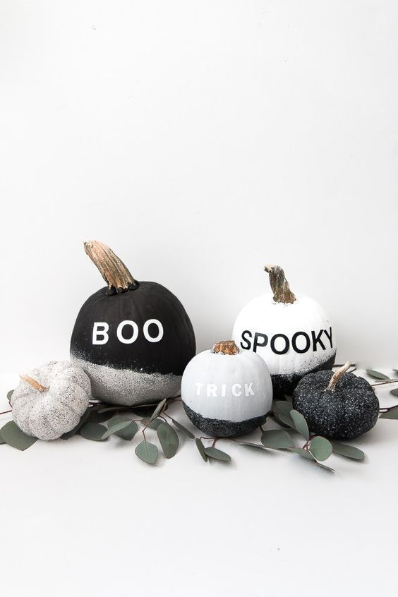 minimalist Halloween pumpkins with letters and glitter plus greenery are a very stylish idea to rock