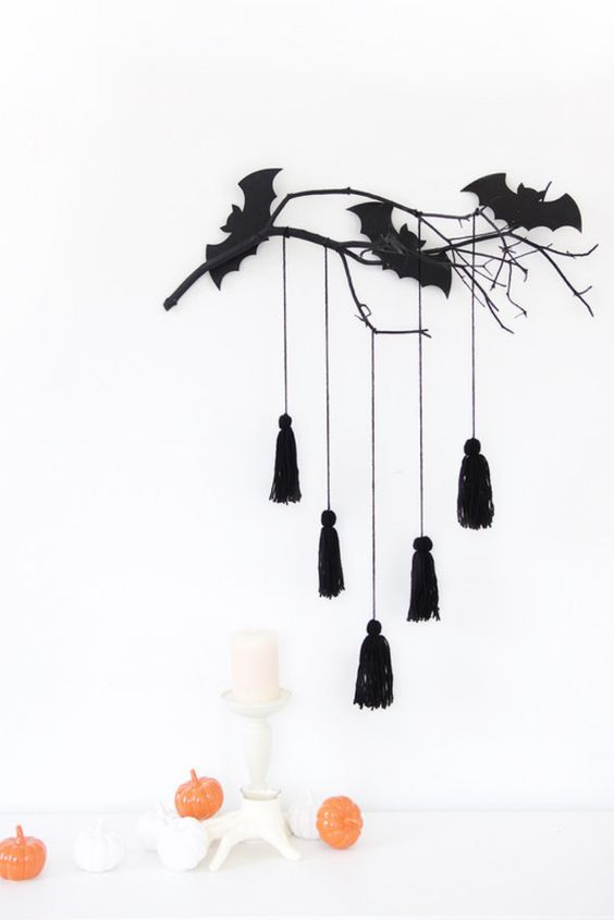 minimalist Halloween styling with a black branch with bats and tassels, mini pumpkins and a white candle in a candeholder