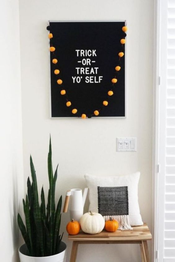 minimalist Halloween styling with a black sign and orange pompoms, white and orange pumpkins