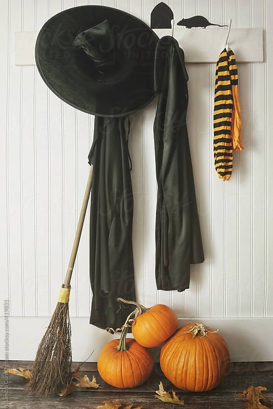 minimalist Halloween styling with black robes, a large hat, pumpkins, leaves and a broom is easy to recreate