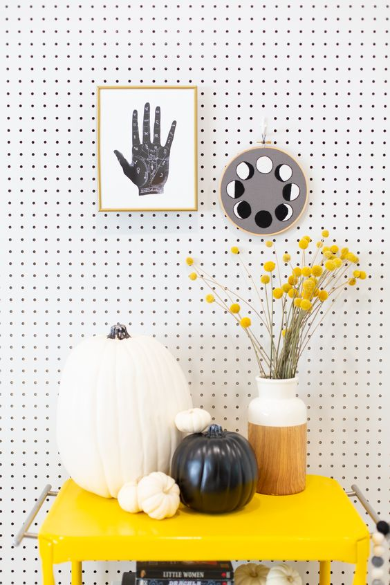 minimalist and bright Halloween decor with a lunar cycle and palm artwork, black and white pumkins on a yellow cart