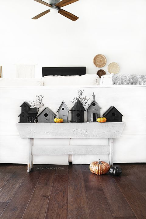 minimalist Halloween decor with grey and black birdhouses, mini pumpkins and larger ones on the floor