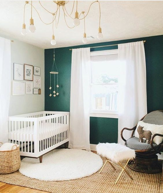 a beautiful nursery with a jute rug, a cool bulb chandelier, a rattan chair and an emerald statement wall