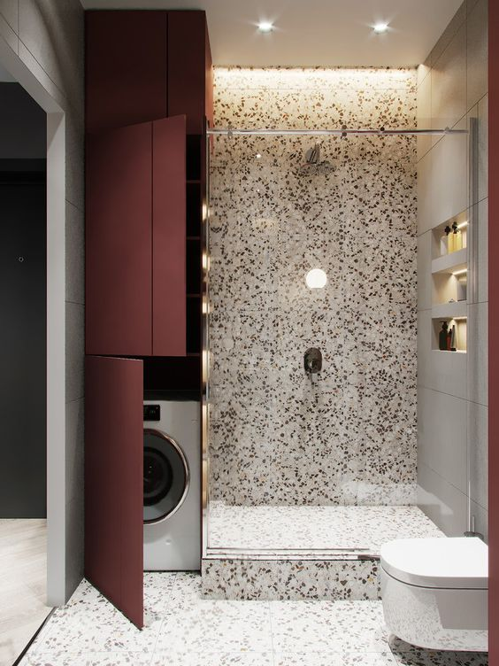 a bright bathroom done with terrazzo with a washing machine hidden by the shower space and behind burgundy doors