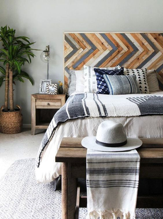 a bright wooden headboard done with a pattern and muted colors to add a relaxed boho feel to the bedroom