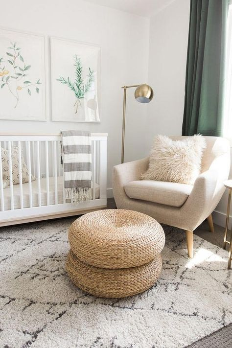 a chic and neutral plus gender-neutral space with a crib, jute ottomans, a comfy chair and a stylish floor lamp