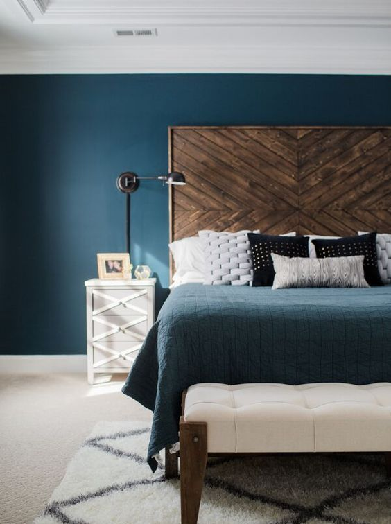 a large dark stained wooden headbard with a chevron pattern gives a texture to the bedroom