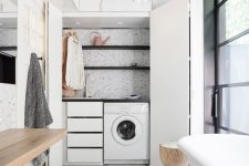 03 a mini laundry hidden in the contemporary bathroom, with drawers, shelves and open shelves plus folding doors