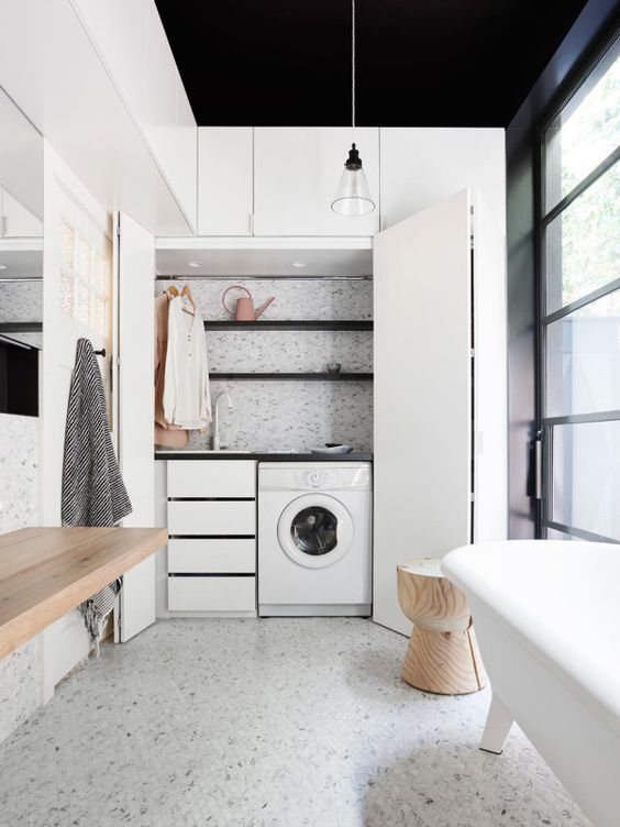 a mini laundry hidden in the contemporary bathroom, with drawers, shelves and open shelves plus folding doors