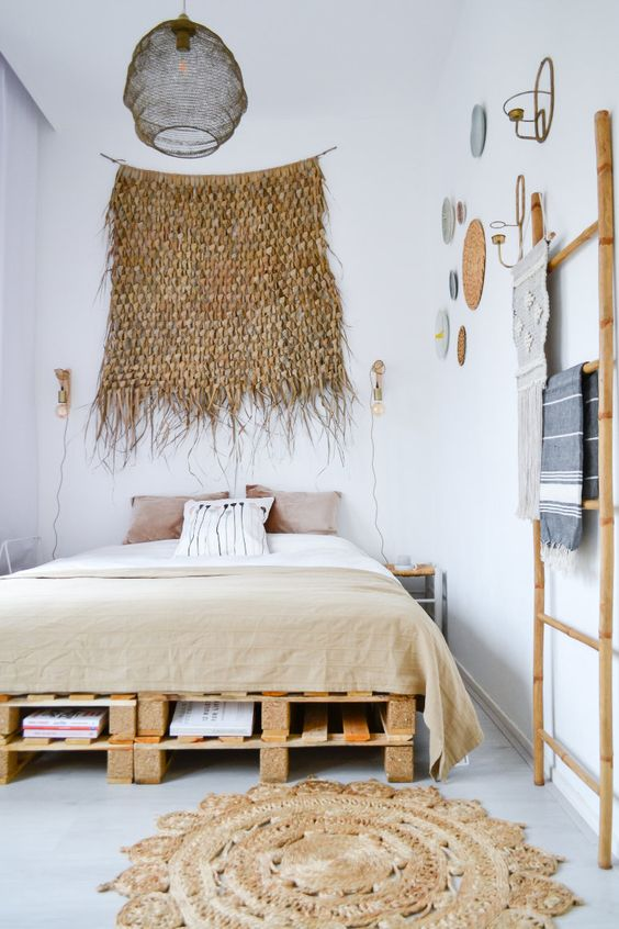 a comfy pallet bed with several layers of storage inside perfectly fits a boho chic bedroom