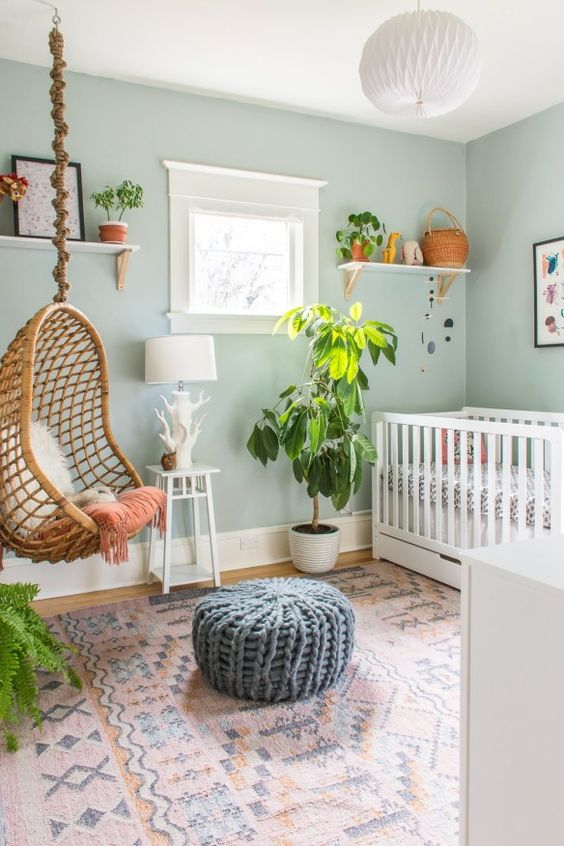 a cool boho-inspired nursery with aqua walls, a hanging rattan chair, a knit ottoman and a boho rug