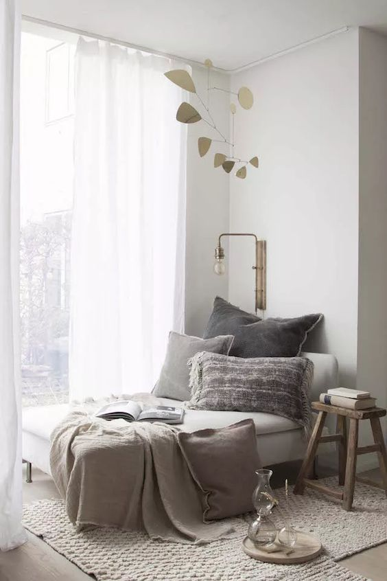 a grey lounger with pillows and blankets, a stylish wall sconce and a wooden stool are nice for decorating a reading nook