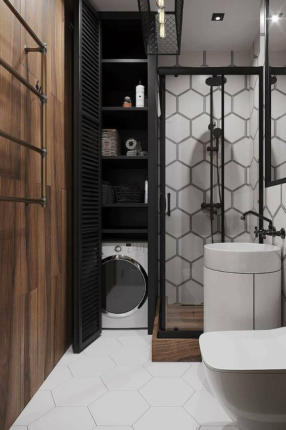 a modern monochromatic bathroom with a hidden wahsing machine and storage space next to the shower