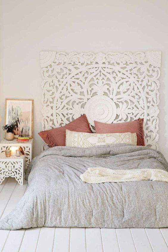a white headboard made of an ornate wooden screen and matching nightstands