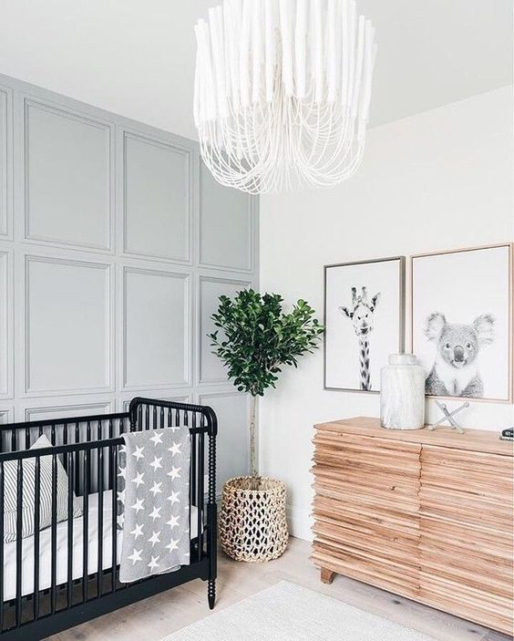 an airy and welcoming neutral nursery with a black crib, a grey paneled wall, a potted plant and a cool dresser