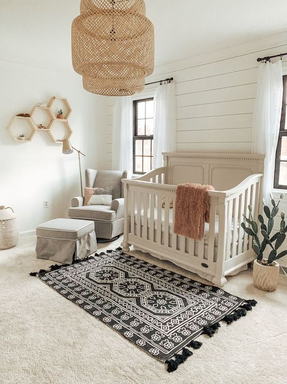 a boho meets vintage nursery with a wicker lampshade, hex shelves, a boho rug, grey furniture is very stylish and bold