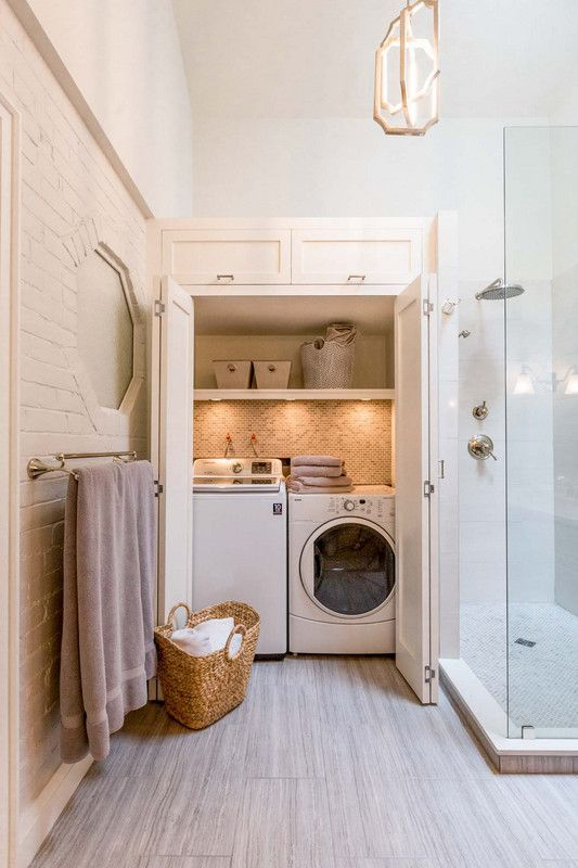 a small laundry hidden right in the bathroom, with built in lights and folding doors is a very comfortable solution