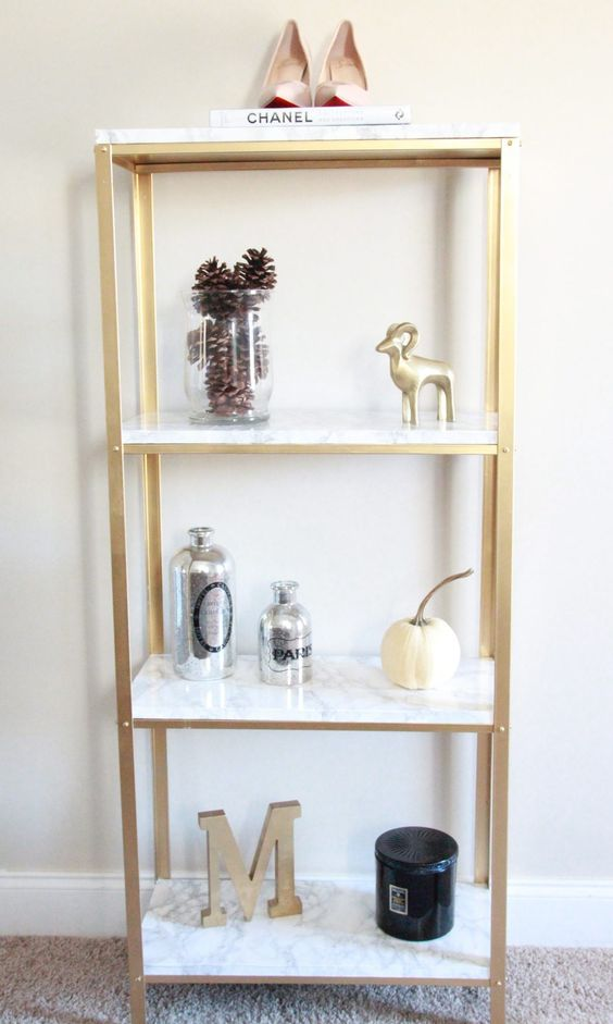 an IKEA Hyllis hack with gold spray paint and marble contact paper will add glam to the space