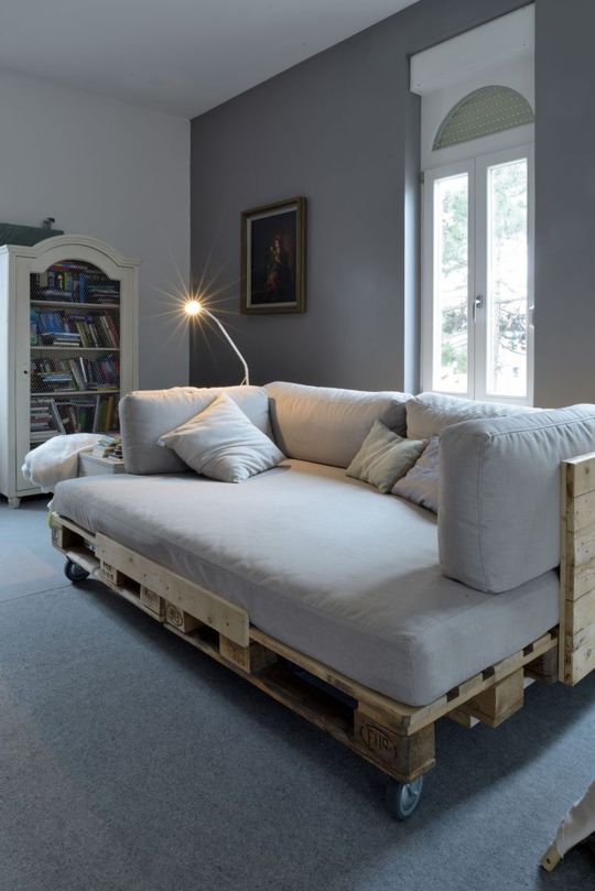 a pallet daybed with a back, casters and a comfy matress and pillows to make napping here comfy